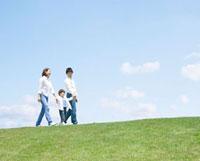 手を繋いで丘を歩く家族