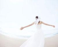 両手を広げて海辺に立つ新婦