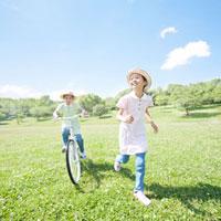 自転車に乗る女の子と走る女の子 11004091340  写真素材・ストックフォト・画像・イラスト素材 アマナイメージズ