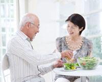笑い合って食事をするシニア夫婦
