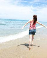 海辺を走る女性の後ろ姿