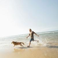 波打ち際を走る男性と犬
