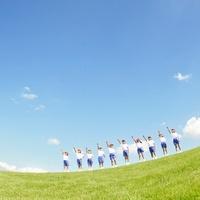 空を指さす体操服姿の小学生