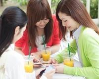 スマートフォンを持って笑う女性達