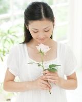 バラの香りを嗅いで微笑む女性