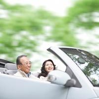 オープンカーでドライブするシニア夫婦