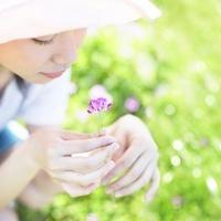 草原でれんげの花を持つ女性