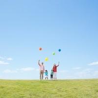 風船を持って草原に立つ日本人家族