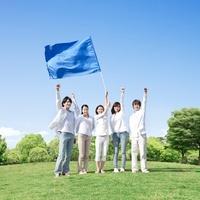 旗を持つ女性と手を挙げる若者達