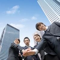 手を重ねる4人のビジネスマンとビジネスウーマン