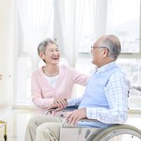 車椅子に座る男性と付き添う女性