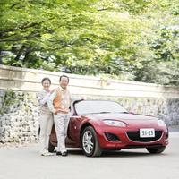 車の横に立つ日本人のシニア夫婦
