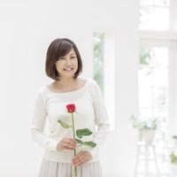 バラの花を持つ中高年女性