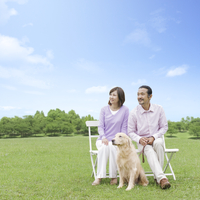 草原でベンチに座る中高年夫婦と犬