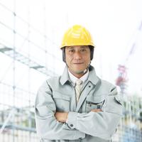 腕を組む工事現場の作業員