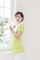 ペットボトルを持ち窓辺に立つ女性