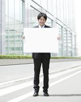 ホワイトボードを持って立つビジネスマン