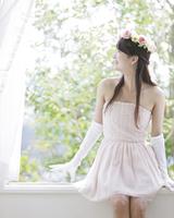 花冠をして窓辺に座る女性