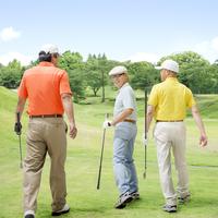 ゴルフクラブを持って歩く3人の日本人男性