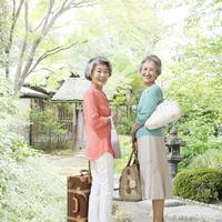 旅行カバンを持つ2人のシニア女性