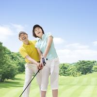 ゴルフをするミドル男女