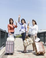 旅行鞄を持って立つ3人の中高年女性