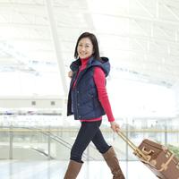 スーツケースをひいて歩く女性