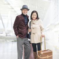スーツケースを持って立つ夫婦