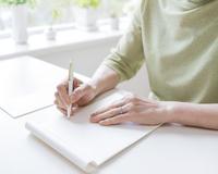 手紙を書くシニア女性の手元
