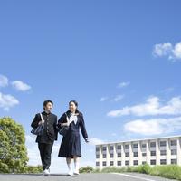 道を歩く日本人の中学生男女