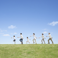 草原を歩く日本人の三世代家族