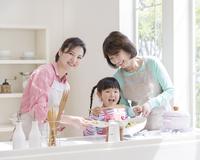 キッチンで料理をする三世代家族