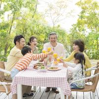 テラスで食事する三世代家族