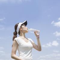 ペットボトルの水を飲む女性