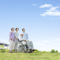 車椅子に乗る男性と家族