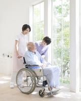 車椅子に乗る男性に話す看護師と女性