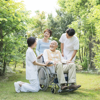車椅子に乗る男性と女性と看護師