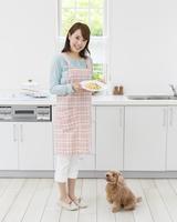 料理を持って立つ女性とトイプードル