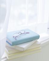 窓辺に置かれた本と眼鏡 11004109602| 写真素材・ストックフォト・画像・イラスト素材|アマナイメージズ