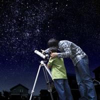 星空の下で望遠鏡を覗く父と息子