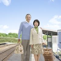 駅のホームに立つ笑顔の夫婦