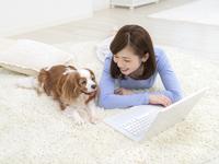 パソコンに向かう女性と犬