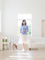 リビングを歩く女性と犬