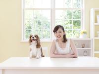 テーブルに向かう女性と犬