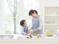 キッチンでお弁当を作る親子