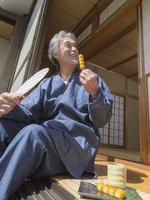 みたらし団子を食べる中高年男性 11004111849| 写真素材・ストックフォト・画像・イラスト素材|アマナイメージズ