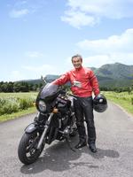 バイクの横に立つシニア男性