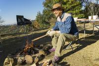 焚き火を起こすシニア男性 11004113741  写真素材・ストックフォト・画像・イラスト素材 アマナイメージズ