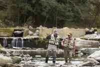 川の中を歩く2人のシニア男性
