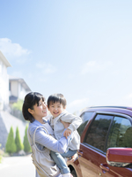 車の前で息子を抱く母親 11004114876| 写真素材・ストックフォト・画像・イラスト素材|アマナイメージズ
